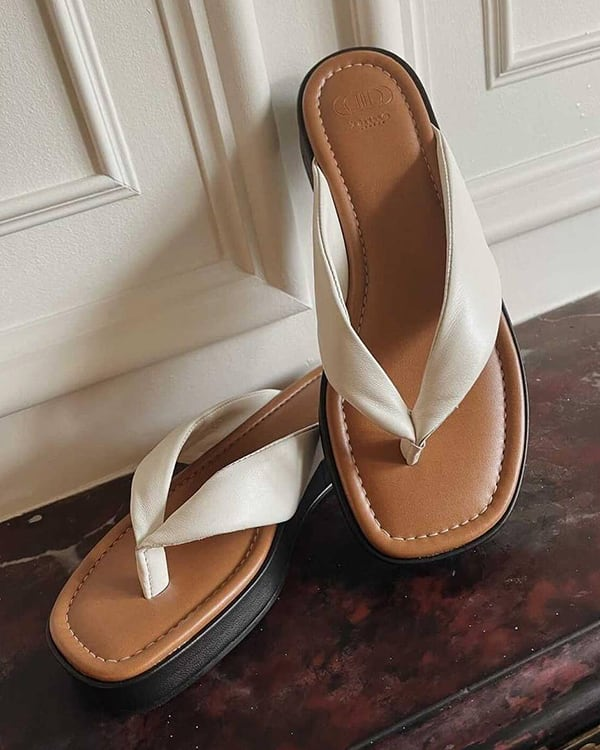 The Longisland sandals in white propped up against a wall