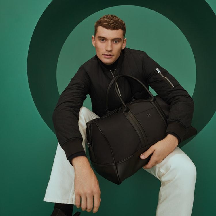 Model holding black bag