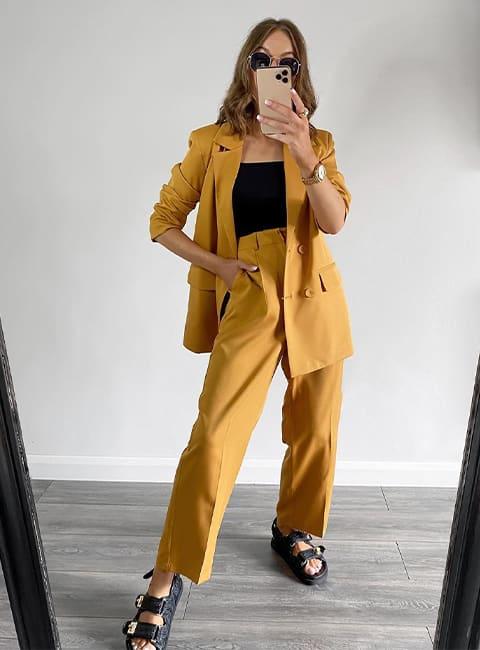 Model taking a mirror selfie wearing the Lockstock sandal