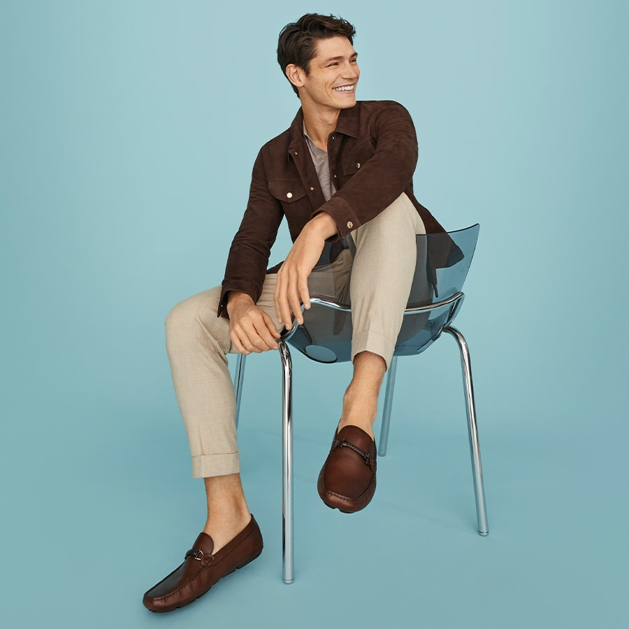 Model sitting on a chair wearing the Beacons driver shoe