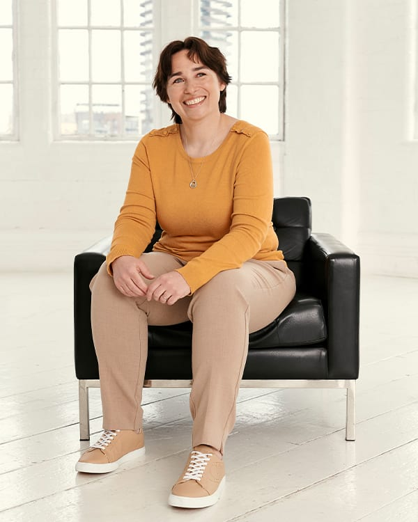 A woman sitting on a chair wearing Dune London shoes