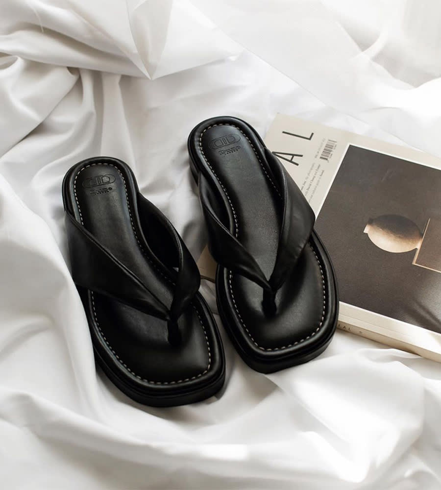 Pair of Longisland sandals in black resting on a table