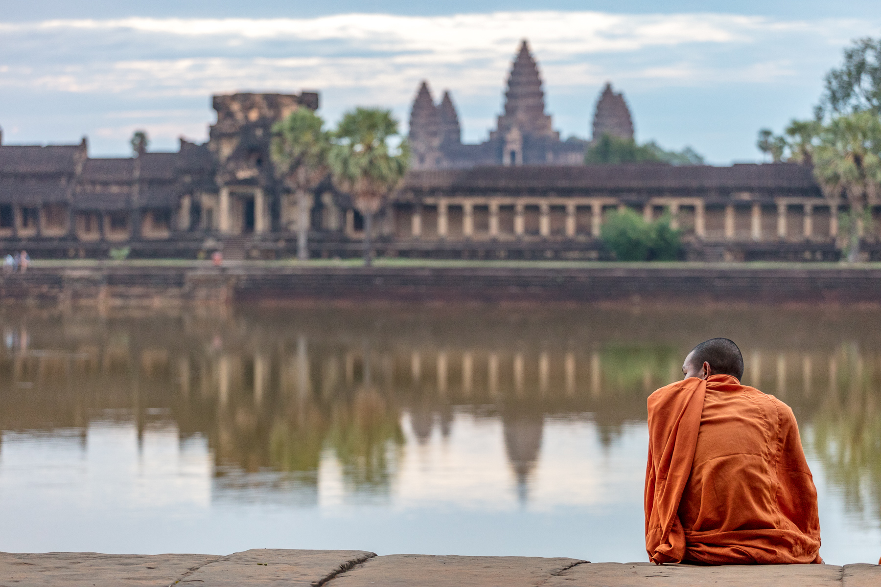 A monk watches the tourists at Angkor Wat