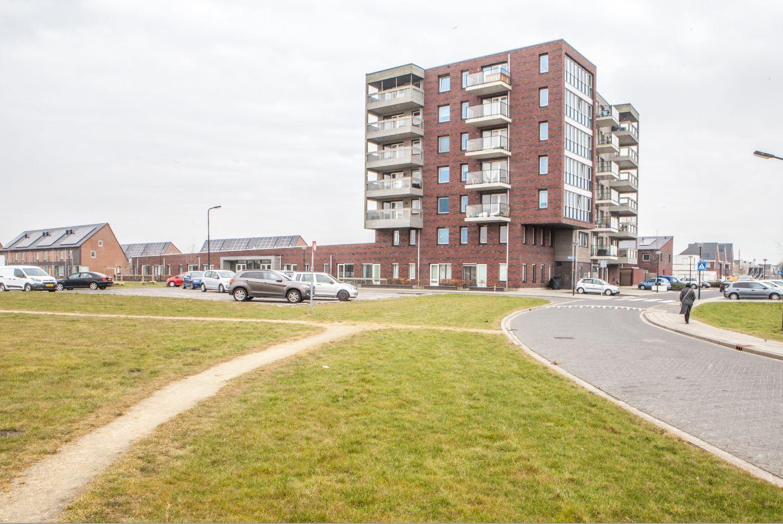 Foto van een appartementen complex met een parkeerplein ervoor