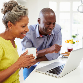 2016 Del Webb Stock Images, MyDWBenefits_420_couplesearchforhomeonline.jpg; Mature African American couple using a laptop in a kitchen