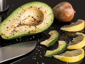 rozkrojené avokádo s nožem a citronem