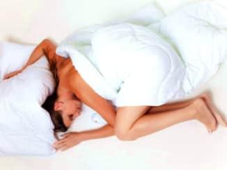 žena v posteli přikrytá peřinou