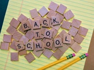 nápis Zpět do školy na dřevěných kostičkách a dvě žluté tužky s gumou