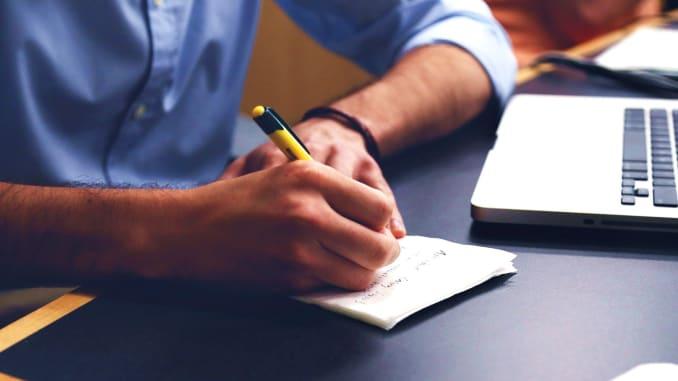 muž u psacího stolu s tužkou a papírem a notebookem