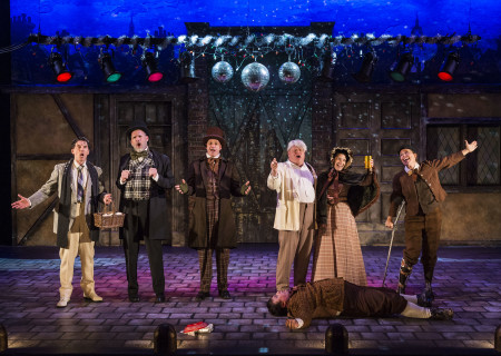 "(L–R) Dan Castellaneta, Ron West, Brian Stepanek, Frank Caeti (prone), Larry Joe Campbell, Amanda Blake Davis, and Jean Villepique in The Second City's ""A Christmas Carol: Twist Your Dickens!"" at the Douglas."