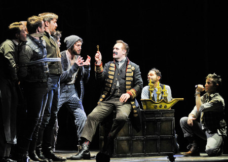 """(Center, L–R) Ian Michael Stuart, John Sanders (seated on trunk), Lee Zarrett, and Carl Howell with the company of """"Peter and the Starcatcher."""""""