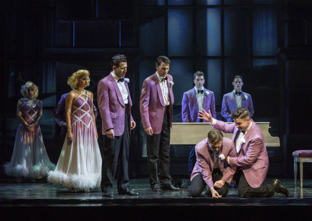 "(L–R) Liberty Cogen, Lindsay Moore, Matt Bailey, Douglas Williams, Shayne Kennon, Chris Dwan (kneeling front), Will Taylor, and Will Blum in ""Harmony"" at the Ahmanson Theatre."