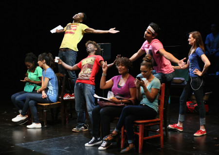 """(L–R) Ameenah Kaplan, Linda Park, Aaron Jennings (yellow), Lorenz Arnell (red) Deidrie Henry (purple), Tessa Thompson (light blue), Erick Lopez and Deborah Puette in a special DouglasPlus reading of """"Facing Our Truth: Ten-Minute Plays on Trayvon, Race and Privilege"""" at the Kirk Douglas Theatre."""