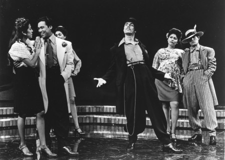 "L-R: Rose Portillo as Della, Daniel Valdez as Henry, Evelina Fernandez (partially seen), Edward James Olmos, Rachel Levario and Mike Gomez in the world premiere of ""Zoot Suit"" at the Mark Taper Forum. Written and directed by Luis Valdez and presented in association with El Teatro Campesino, the revival of ""Zoot Suit"" will play January 31 through March 12, 2017, as part of Center Theatre Group/Mark Taper Forum's 2017-2018 season at the Los Angeles Music Center. Tickets for the Mark Taper Forum's 50th anniversary season are currently available by season ticket membership only. For information and to charge season tickets by phone, call the Exclusive Season Ticket Hotline at (213) 972-4444. To purchase season memberships online, visit www.CenterTheatreGroup.org/Taper. Contact: CTGMedia@ctgla.org / (213) 972-7376. Photo by Jay Thompson."