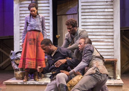 "L-R: Sameerah Luqmaan-Harris (standing), Larry Powell, Sterling K. Brown, Russell G. Jones and Julian Rozzell Jr. in ""Father Comes Home From The Wars (Parts 1, 2 & 3)"" at Center Theatre Group/Mark Taper Forum. Written by Suzan-Lori Parks and directed by Jo Bonney, the West Coast premiere of ""Father Comes Home From The Wars (Parts 1, 2 & 3)"" plays April 5 – May 15, 2016. For tickets and information, please visit CenterTheatreGroup.org or call (213) 628-2772. <br />