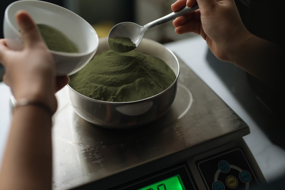 A man holds a bowl and a scoop over a bin of fresh green kratom powder