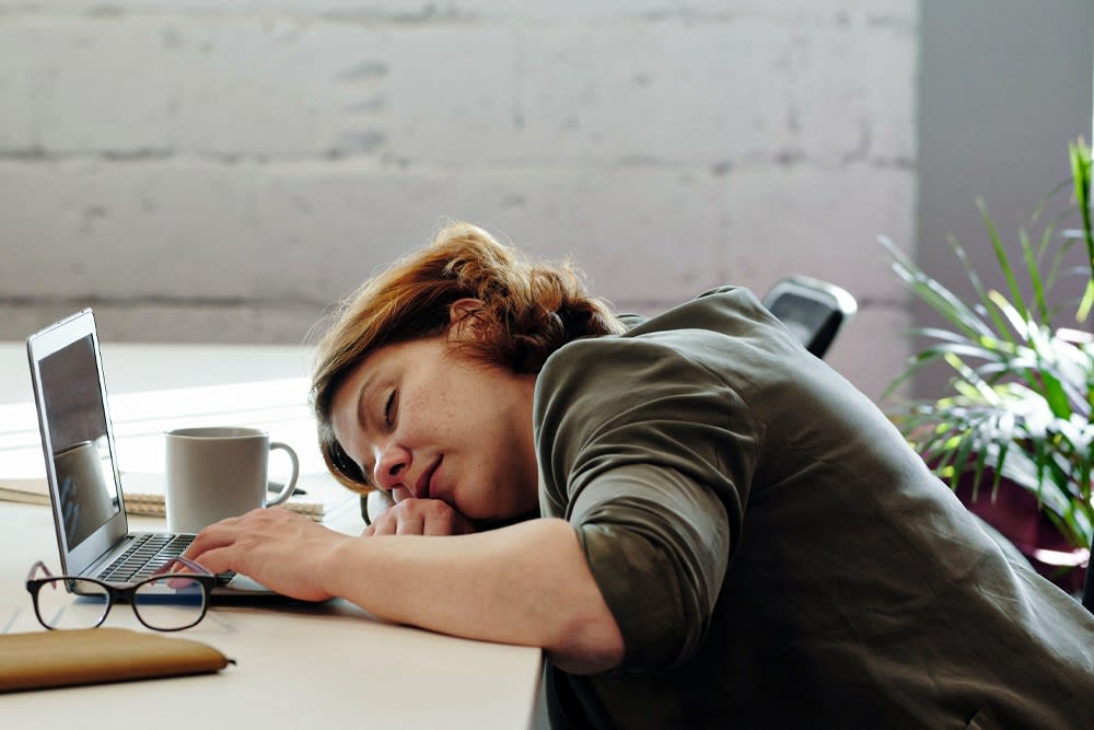 An exhausted woman sleeps at her desk