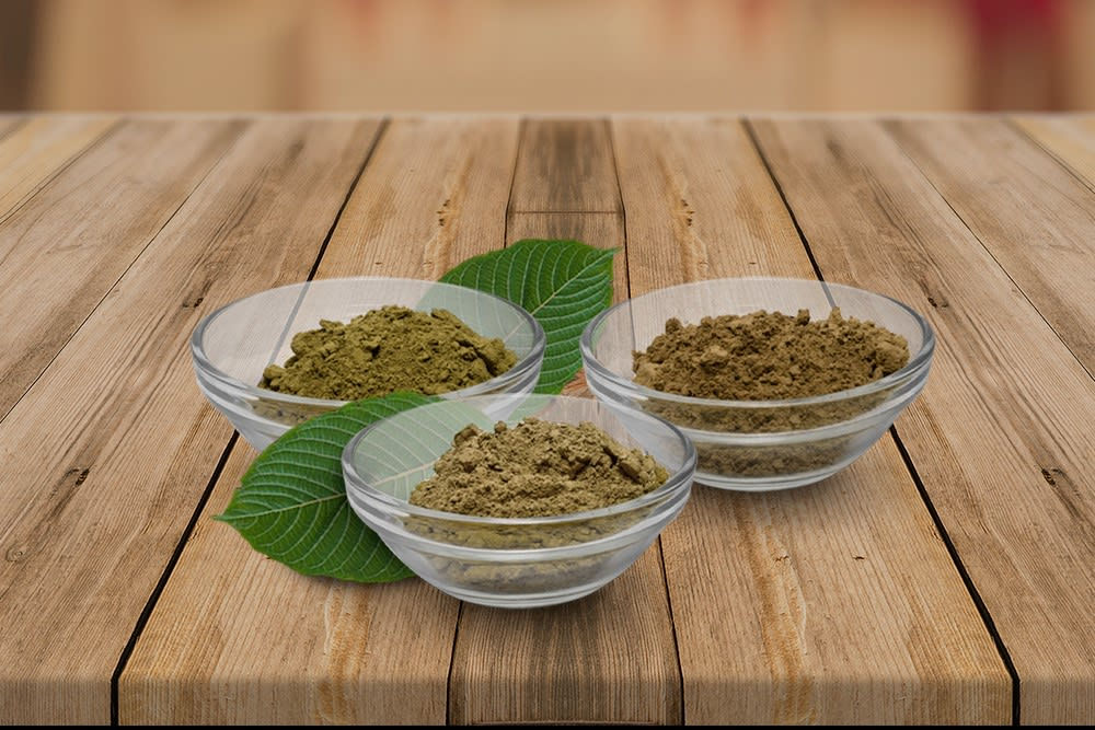 Three bowls of kratom sit on a slatted wooden surface