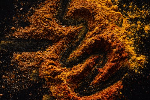 Several orange piles of turmeric powder sit on a dark background