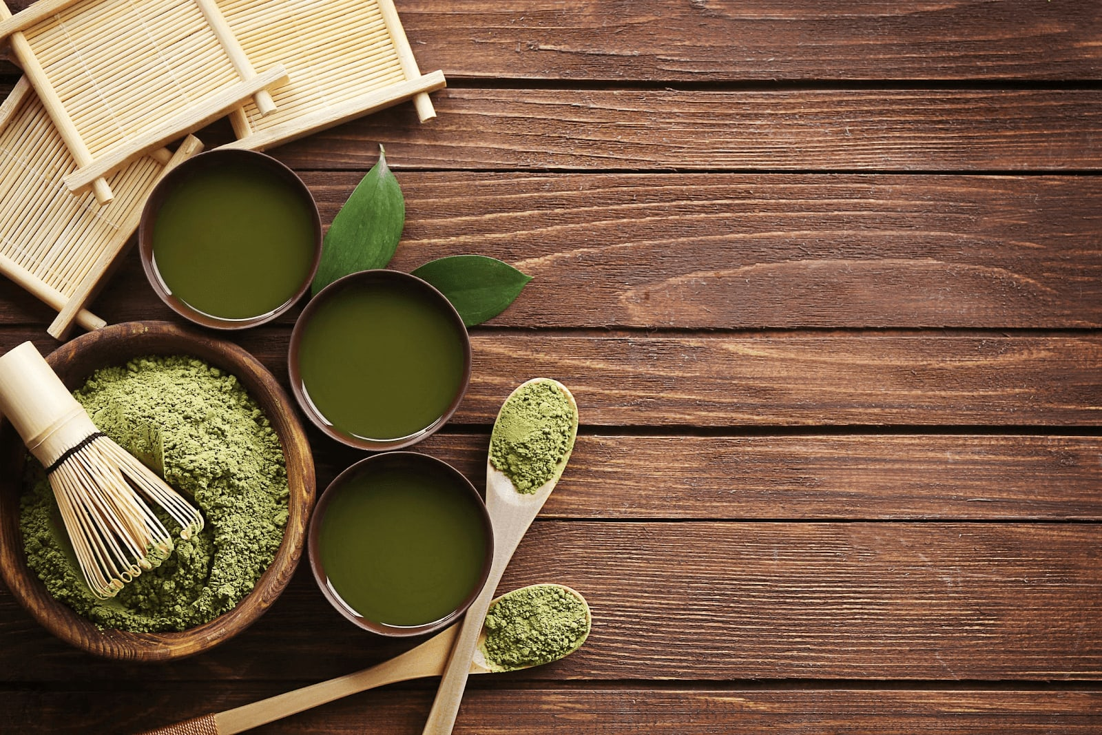 Liquid and powdered kratom extract in bowls and spoons on a wooden table.