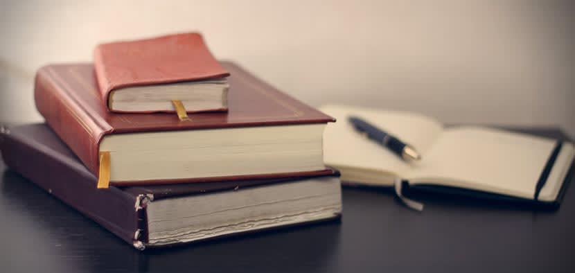 Three law books stacked in front of a notebook