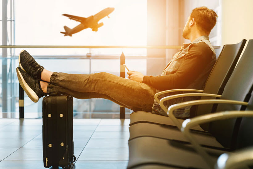 A man sitting with his feet propped on a suitcase watching a plane take off through an airport window