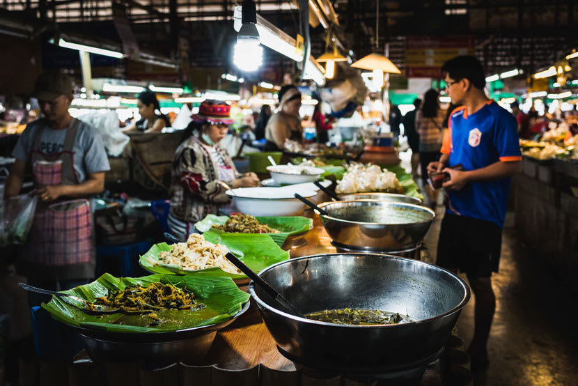 Man walks through busy food market in Thailand