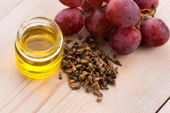 A pile of grapeseed sits beside red grapes and a glass of yellow oil