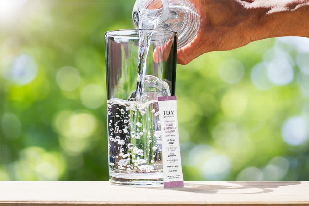 A bottle of CBD water sits next to a Joy Organics CBD Energy Drink