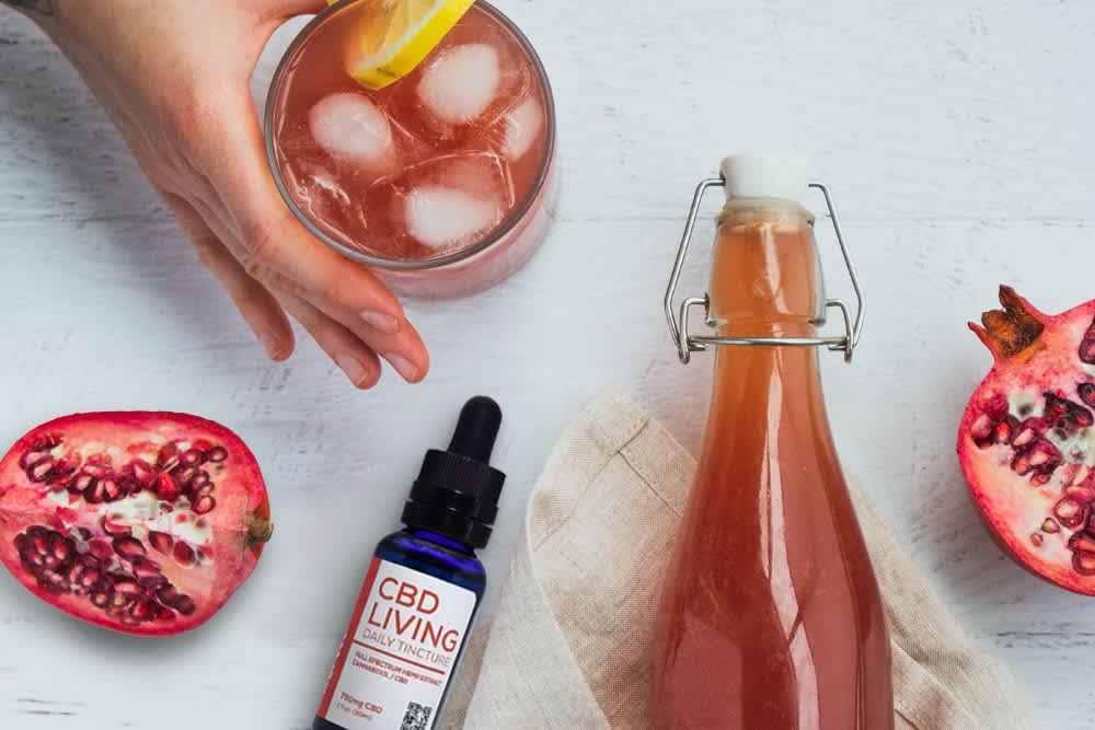A bottle of CBD kombucha sits next to a ripe pomegranate and a bottle of CBD tincture