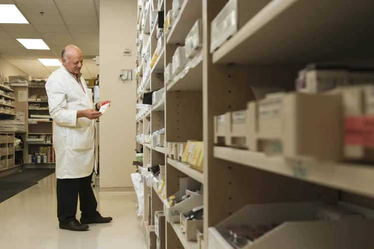 A male pharmacist dressed in a white coat is standing next to tall shelves of pharmacy inventory and examining a drug.