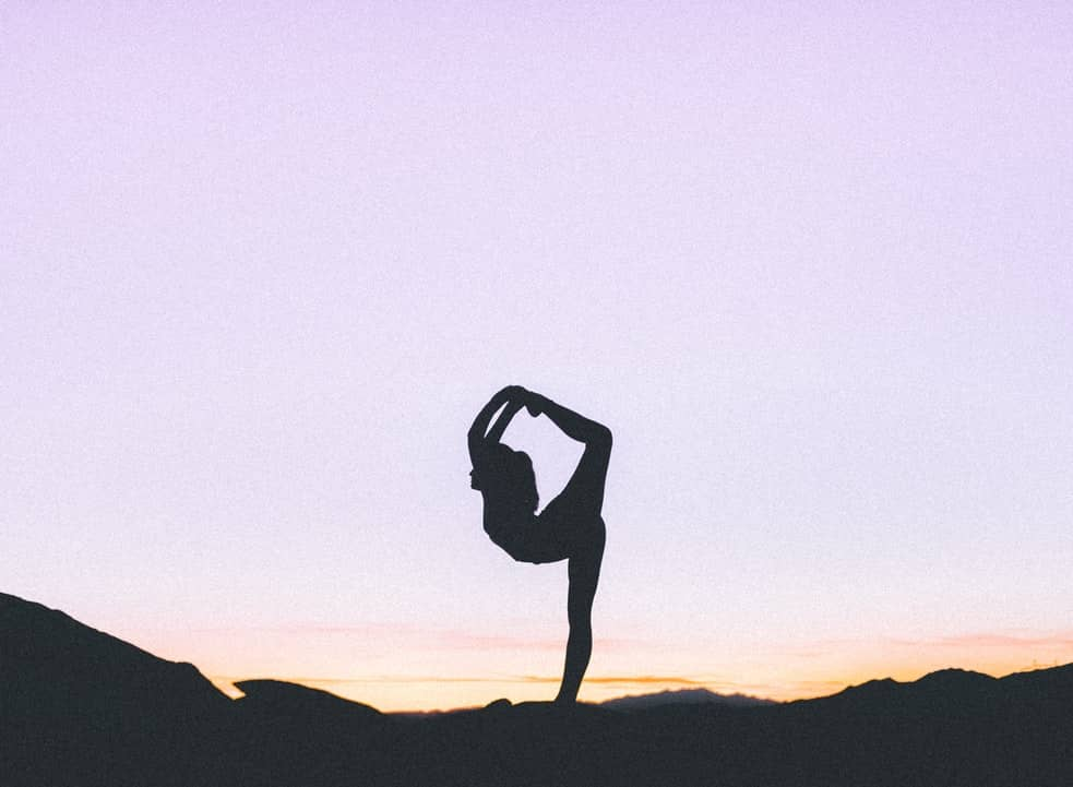 A woman stretches along a horizon