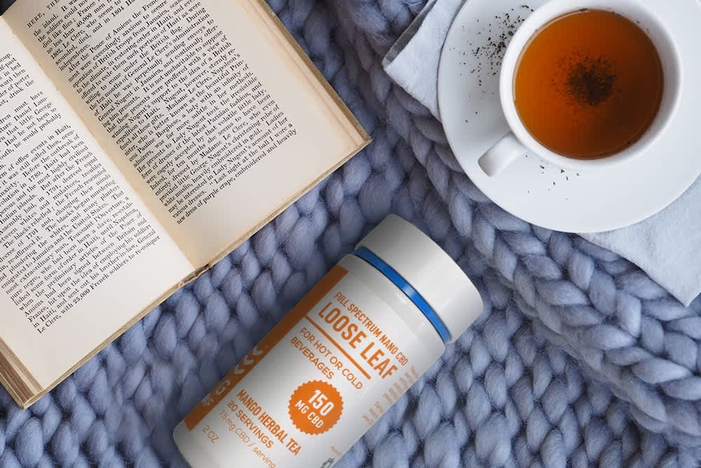 A bottle of CBD infused tea sits on a blue knit surface alongside a book and cup of tea