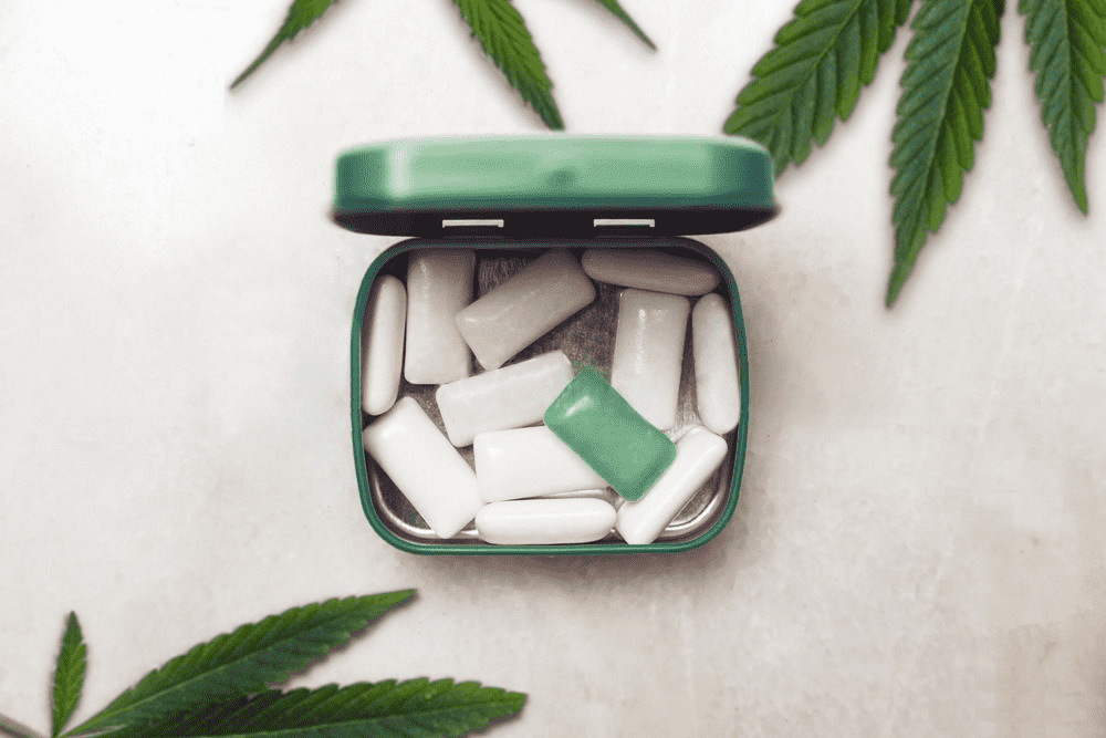A tin of white and green CBD gum sits on a white background