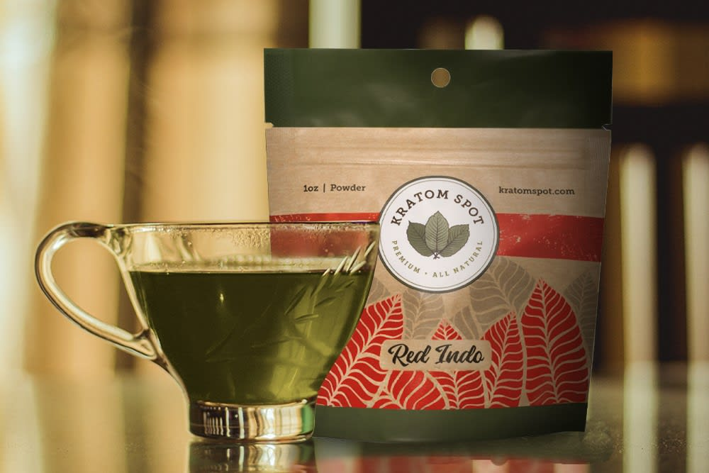 A cup of delicious kratom tea sits in front of a pouch of red indo kratom