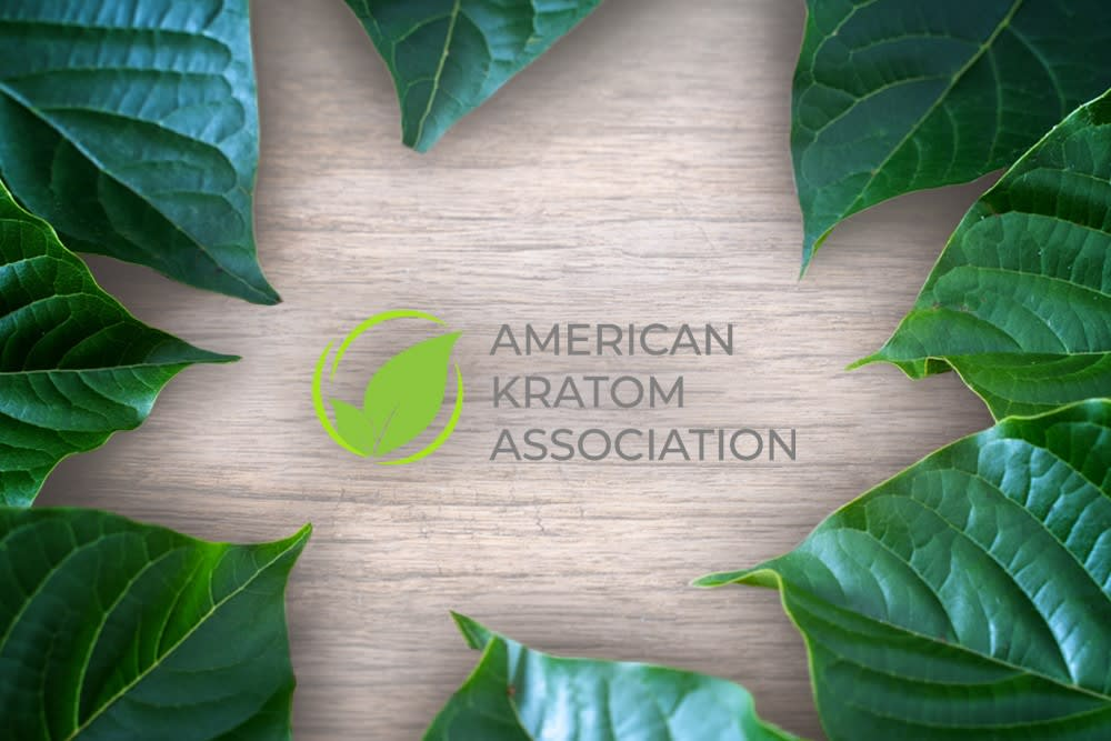 The American Kratom Association logo sits on a wood background, surrounded by leaves