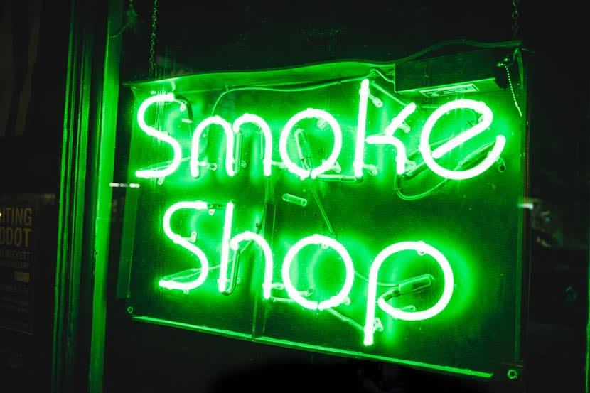 A green neon smoke shop sign