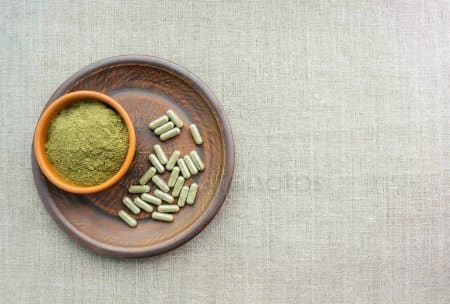 A photo of a bowl filled with kratom powder, sitting on top of a plate of kratom capsules.