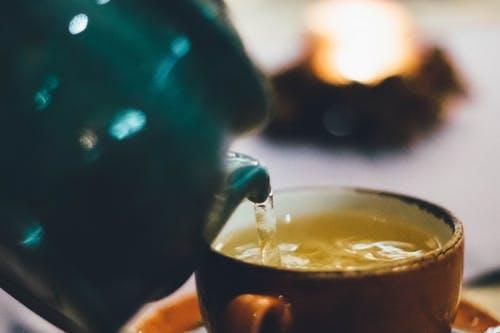 A photo showing a miniature teapot pouring tea into a teacup.