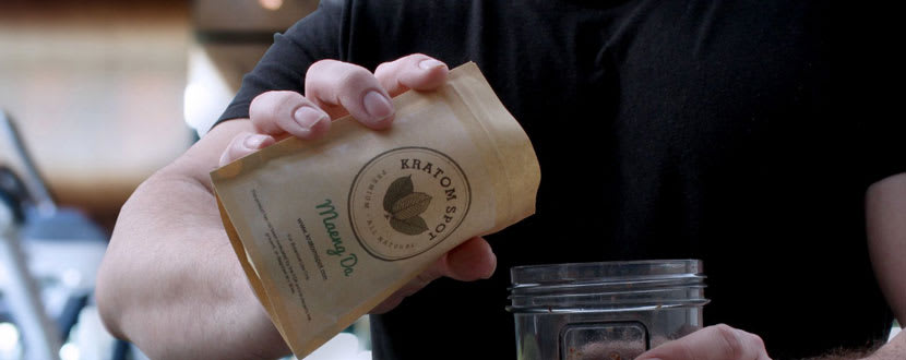A man pouring Kratom into the mouth of a jar