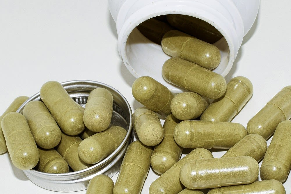 A pile of green kratom capsules sits on a white background