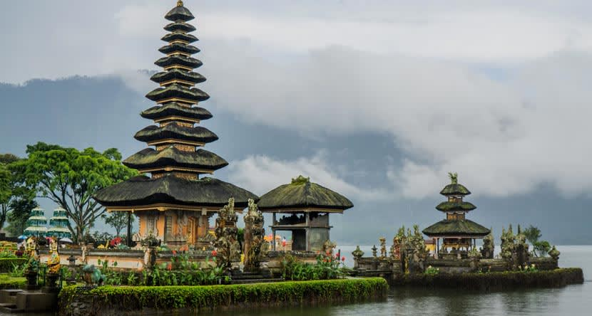 A temple in Bali surrounded by greenery with a lush mountain in the background