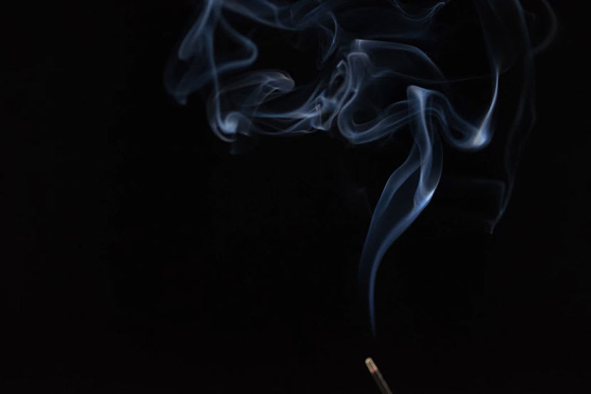 Smoke curls up from a burning incense stick