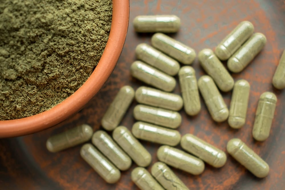 A bird's eye view of kratom powder (in focus) and a lot of kratom capsules (out of focus).