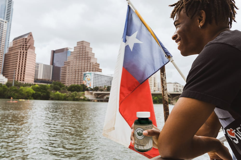 A man celebrates on a river in Texas by taking kratom now that kratom is legal under the Texas Kratom Consumer Act