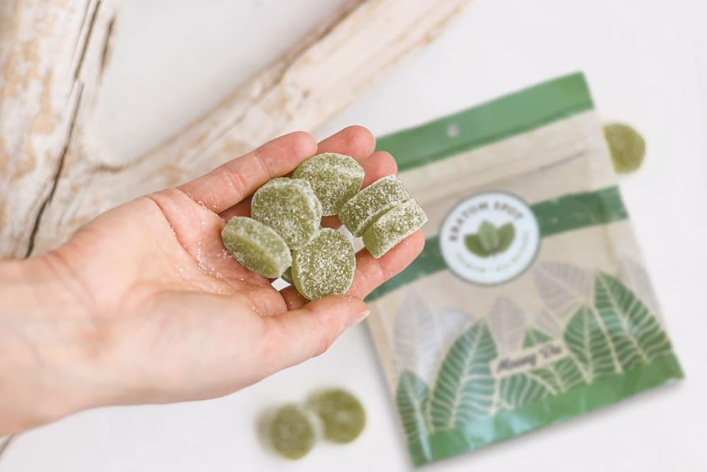 A hand holding a handful of green kratom edibles atop a bag of Kratom Spot kratom.