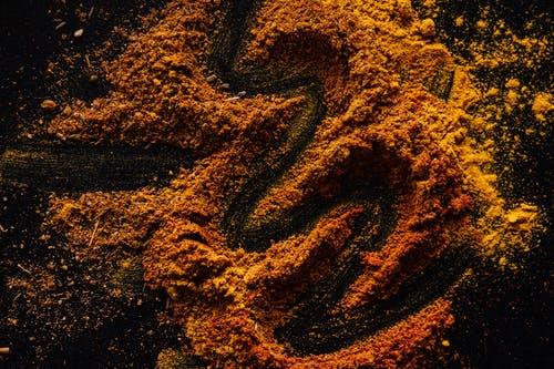 Several orange piles of turmeric powder sit on a dark background