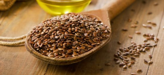 A spoon full of flax seed sits on a light brown table