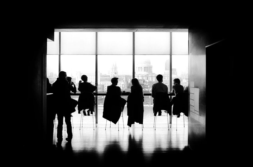 The black silhouettes of people sitting in a room overlooking the DC area