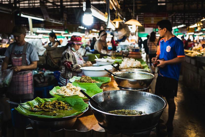 Man walks through busy food market in Thailand